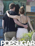 Miley Cyrus and Liam Hemsworth put their arms around each other.