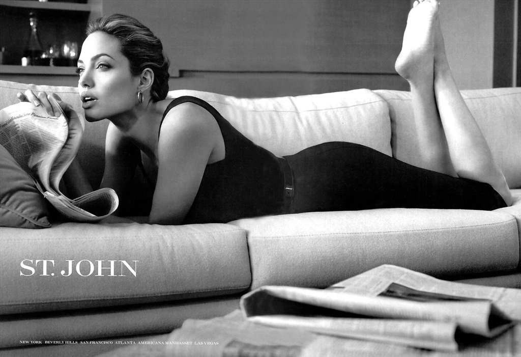 Angelina Jolie lounged on a couch while reading the paper for one of her sexy St. John ads.