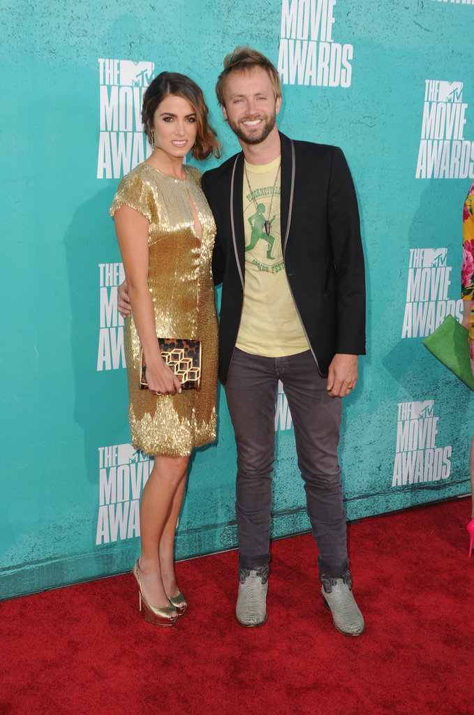 Nikki Reed wore a gold dress and posed with husband Paul McDonald on the red carpet at the MTV Movie Awards.