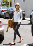 Taylor Swift looked retro sweet and chic in a pair of ankle-cropped trousers and red lips to match her scarlet loafers.