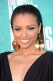 Kat Graham's statement gold earrings offset her black Maria Lucia Hohan gown.