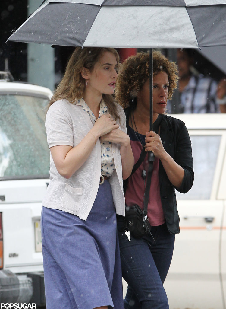 Kate Winslet avoided the rain under an umbrella on the set of Labor Day.
