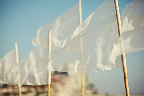 Simple flags made from bamboo stakes and strips of white, gauzy fabric lined the wedding aisle in this beach wedding.  Source