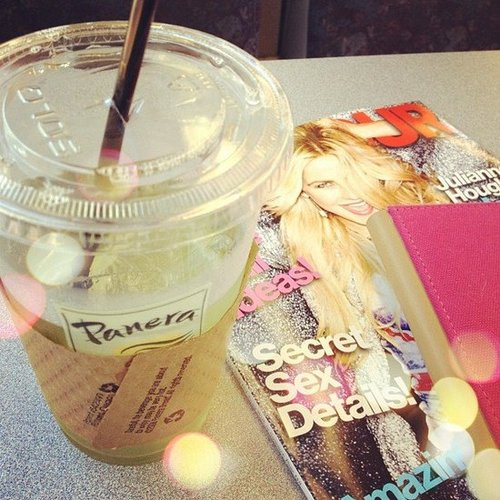 My train ride companions include iced green tea, a magazine, and my Kindle.