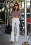Miranda Kerr wore white pants and carried a black leather bag in NYC.