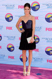 Nikki Reed wore a sexy yet demure cocktail dress by Contrarian New York paired with a metallic clutch and wedges.