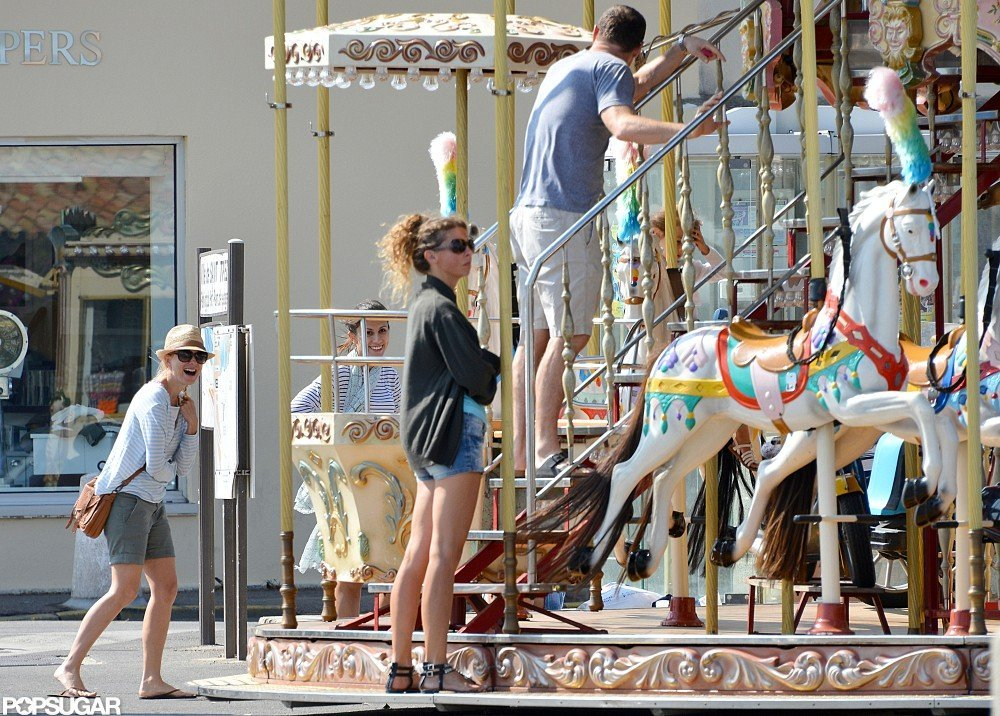 Naomi Watts laughed while Liev Schreiber climbed to the second story of the merry-go-round.