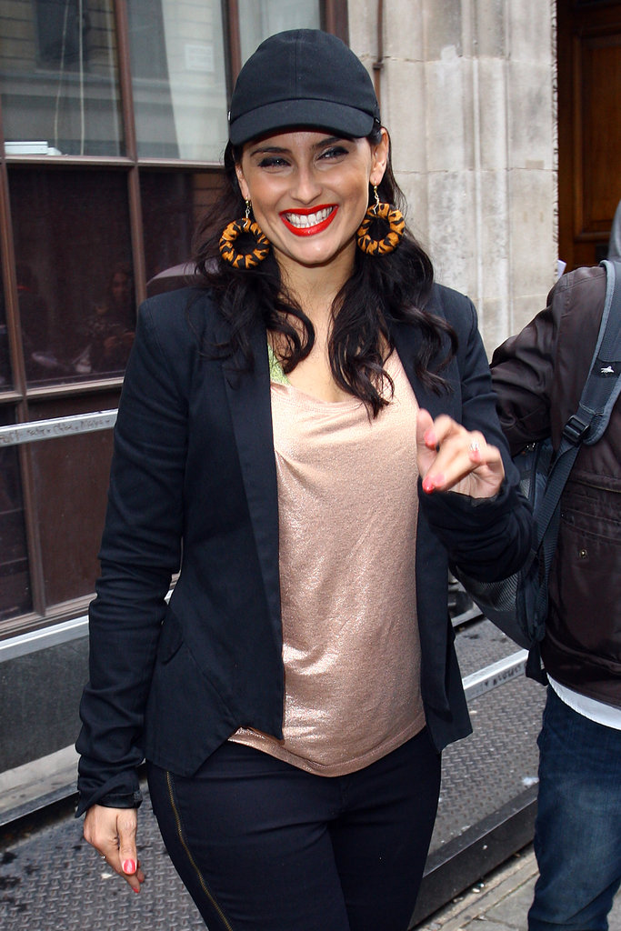 Nelly Furtado paired her dark-denim jeans and blazer with a plain black cap and statement earrings.