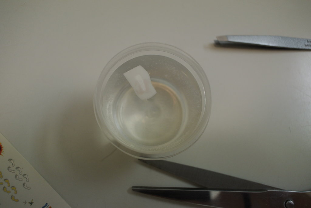 I left it in the water for about 30 seconds, and then picked it up with my tweezers and placed face-down on my nail.