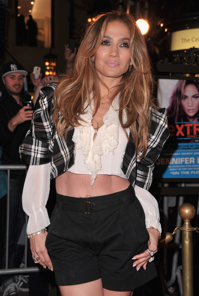 Jennifer Lopez let her tummy peek through while filming a segment for Extra in LA in March 2011.