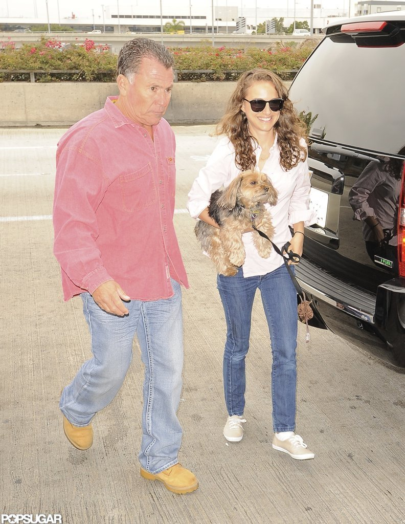 Natalie Portman carried her dog into the airport.