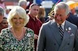 Prince Charles and wife Camilla were entertained by dancers as they waited for the Olympic torch to pass by.
