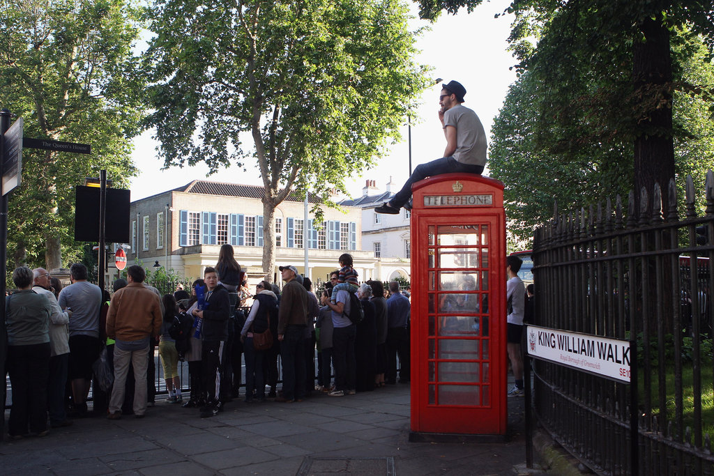 A man sat on top of a red phone box to watch the Olympic torch pass by in London.