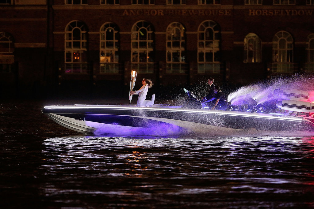 David Beckham arrived on a speedboat with the Olympic torch in tow.