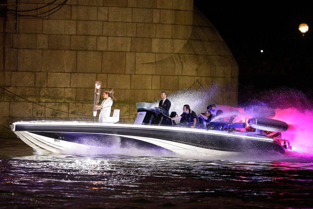 David Beckham made a grand entrance driving the boat with the Olympic torch.