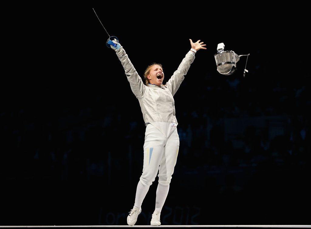 Fencer Olga Kharlan of Ukraine put her arms in the air after winning her match.