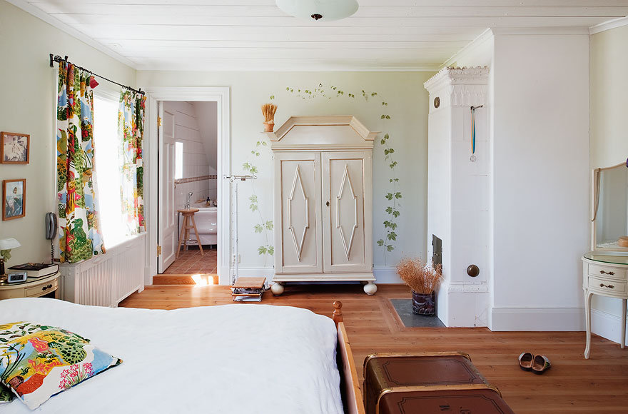 One of the bedrooms at the farmhouse features colorful Josef Frank curtains.