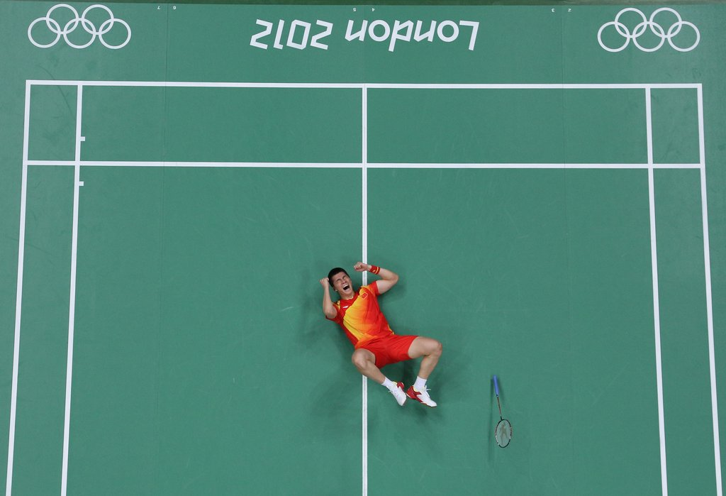 Haifeng Fu of China fell to the ground after winning his badminton match.