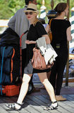 Naomi Watts keeps a low profile in a breezy black dress, black sandals, her go-to fedora, and aviator sunglasses.