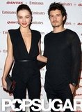 Miranda Kerr wore a deep v-neck jumpsuit as she posed with Orlando Bloom.