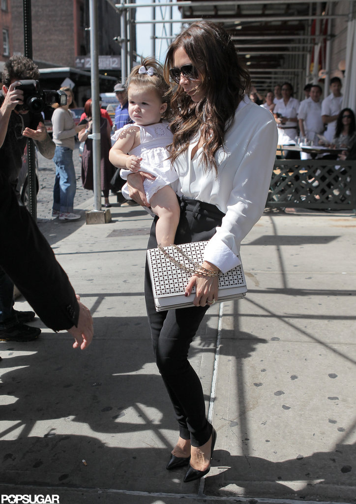 Victoria Beckham carried Harper Beckham to their car.