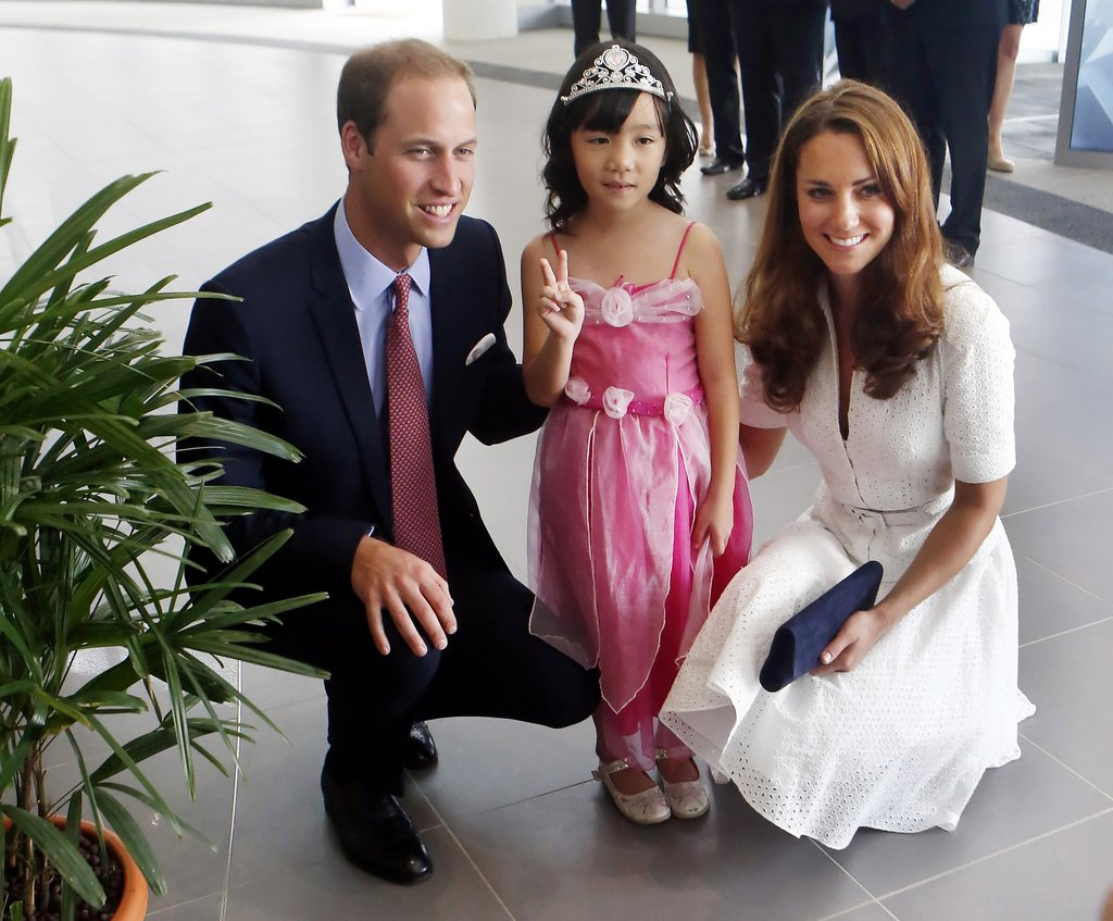 Prince William and Kate posed with a 4-year-old dressed as a princess as they toured a Rolls-Royce factory in Singapore.