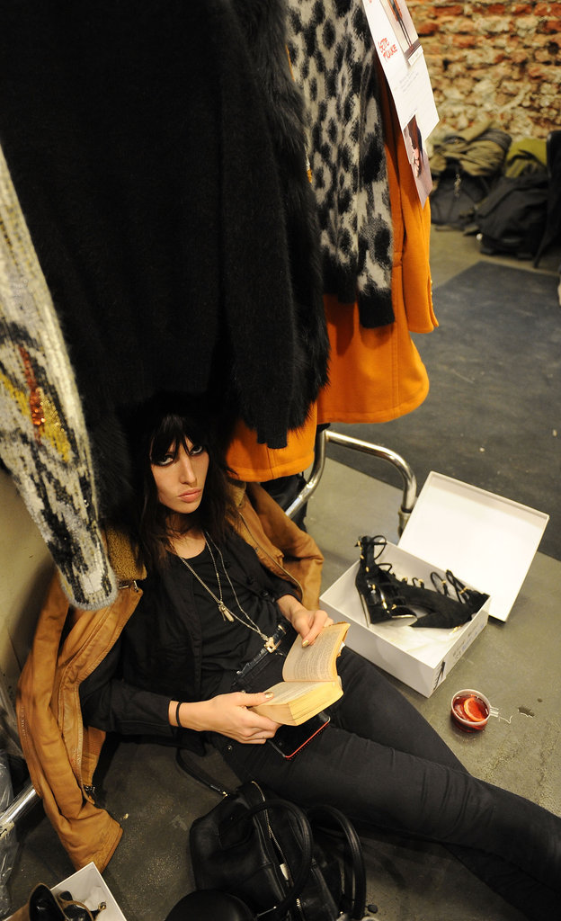 This model looked up from her reading backstage during Milan's Fashion Week in February.
