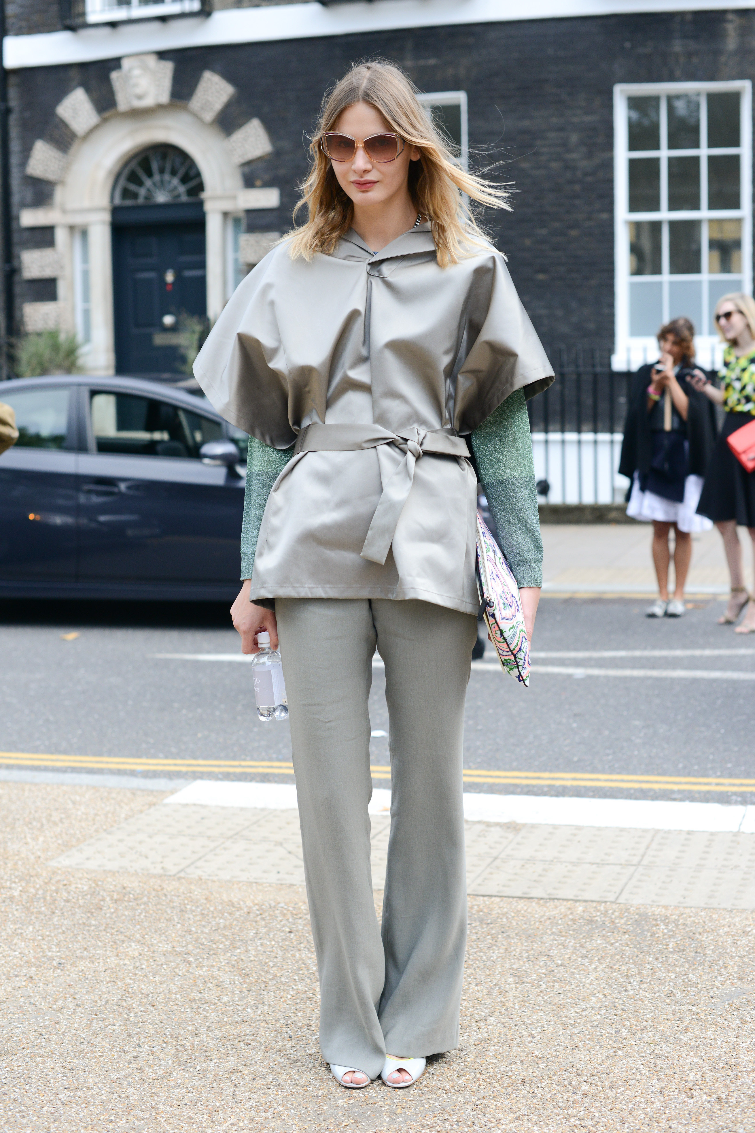 A metallic-sheened poncho can add a more athletic vibe to your trouser combo.