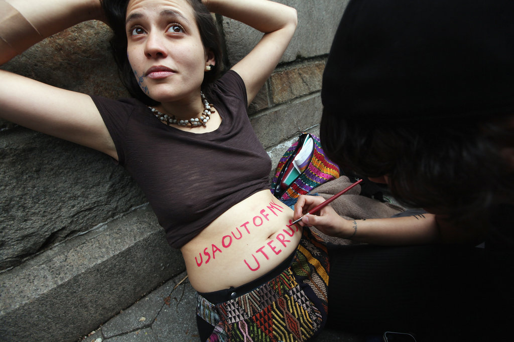 "A female protestor had the message ""USA out of my uterus"" written on her stomach during Occupy's NYC demonstrations."