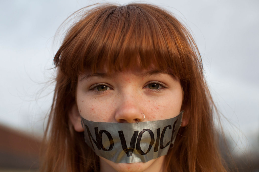A young OWS protestor wore tape over her mouth outside the Iowa Democratic Party headquarters in Des Moines, IA.