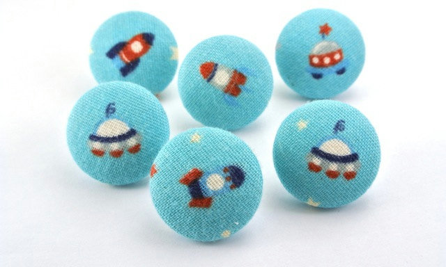These Spaceship-Fabric-Covered Pushpins ($9) would make a great addition to any corkboard.