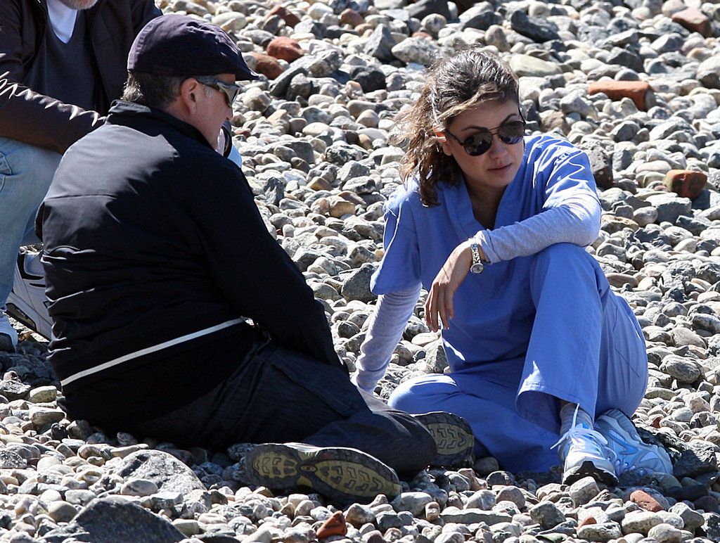 Mila Kunis and Robin Williams sat on the beach.