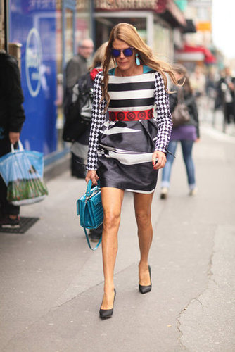 Anna Dello Russo, in a checkered and striped minidress, gives her outfit a bold pop of color via a dark turquoise bag.