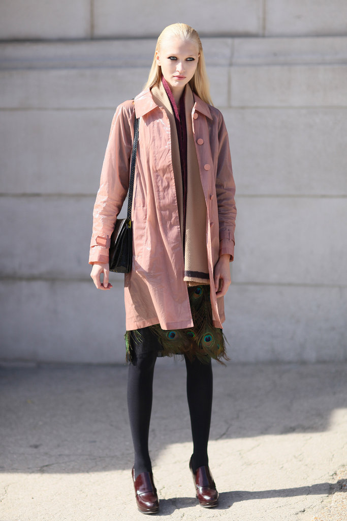 This model showed off her quirky personal styling off the runway, revealing a peacock feather-adorned skirt and a pastel pink coat to contrast her burgundy boots.
