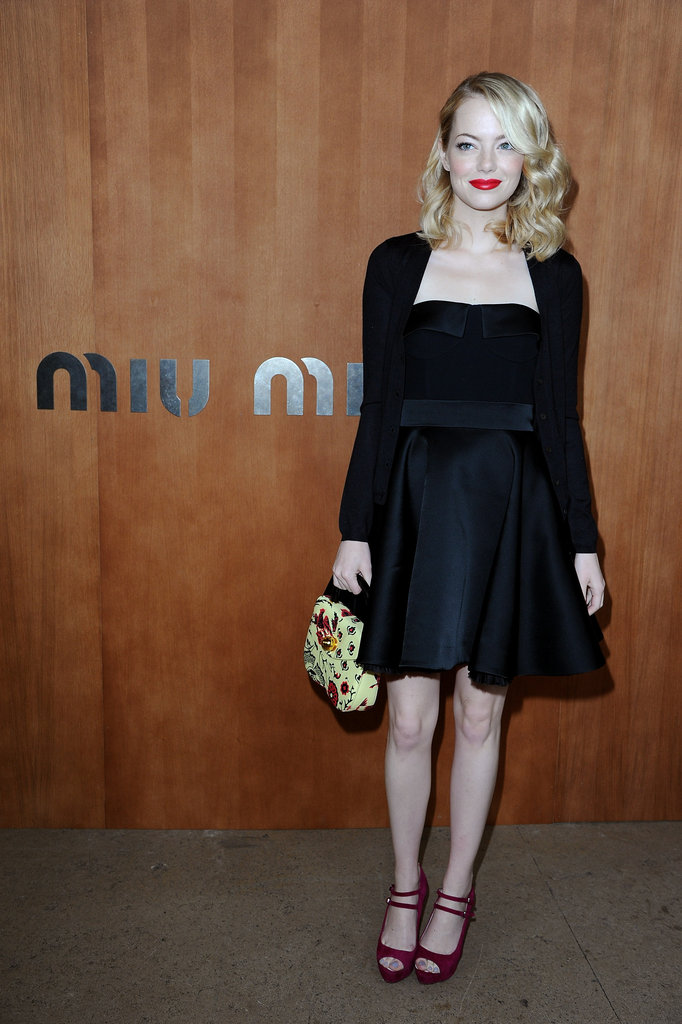 Emma Stone paired her black dress with bold red lips for the Miu Miu show during Paris Fashion Week.