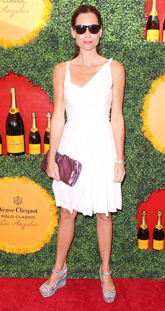 Minnie Driver punched up her white cocktail dress with a bevy of fun accessories, including a metallic pink clutch, printed wedge sandals, and a classic pair of sunglasses.