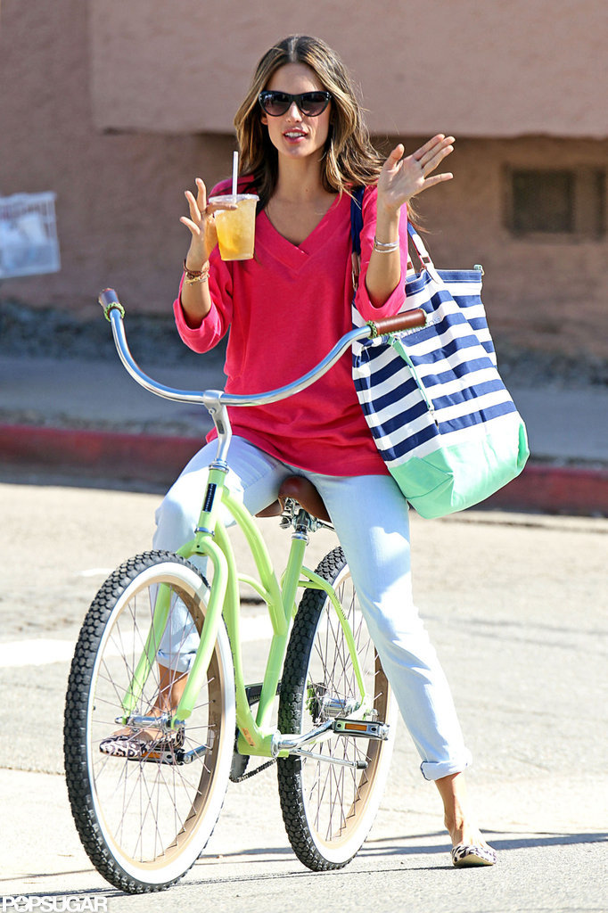 Alessandra Ambrosio balanced a drink and a bag.