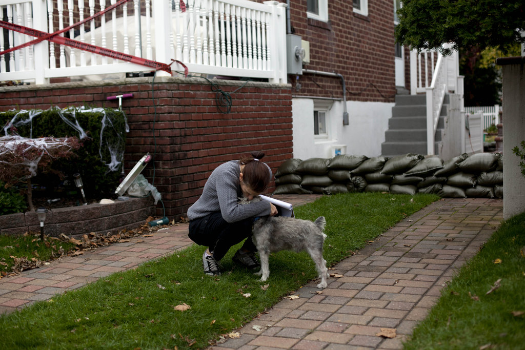 A woman in the Rockaway Beach neighborhood of New York City hugged her dog as she lined sandbags in her yard in preparation for the impending flooding.