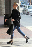 Miley Cyrus carried a black purse.