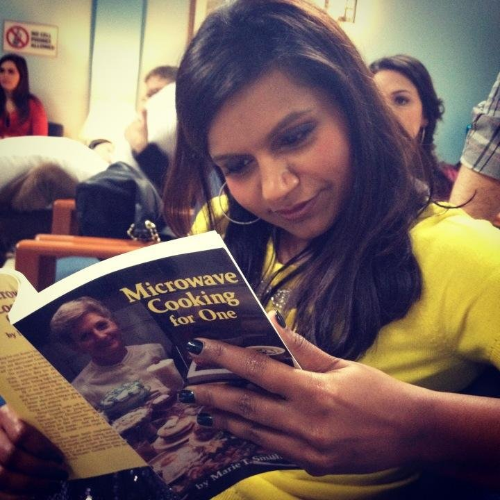 Mindy Kaling leafed through Microwave Cooking For One, aka the saddest prop ever. Source: Twitter user MindyKaling