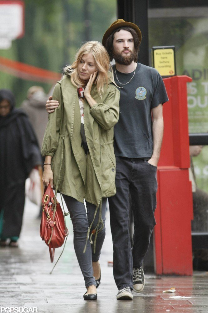 Tom Sturridge put his arm around Sienna Miller in August of 2011 while they walked around London.