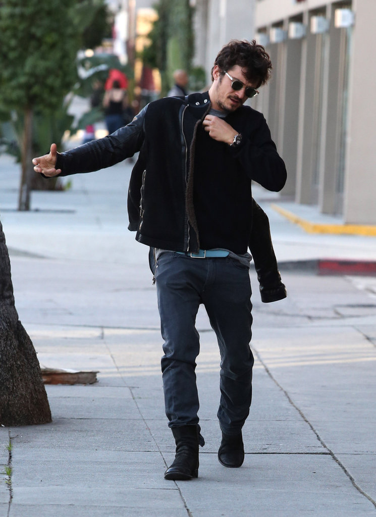 Orlando Bloom put his jacket back on after dropping off a bike.