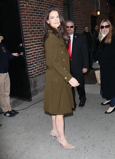 Katie Holmes covered her dress in a coat.