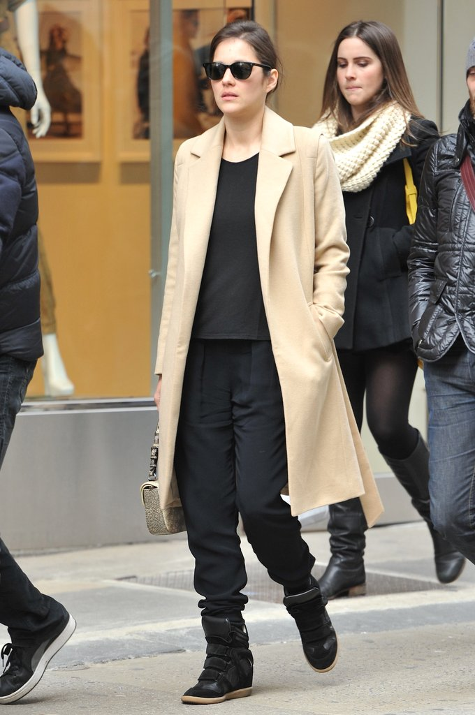 Marion Cotillard looked Parisian chic wearing a luxe camel coat with black Isabel Marant sneakers and matching accompaniments.