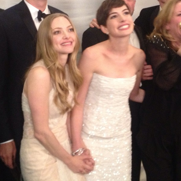 Amanda Seyfriend and Anne Hathaway held hands while celebrating Les Miserables's win. Source: Instagram user goldenglobes