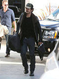 Orlando Bloom wore a hat as he carried his gear to a plane at LAX.