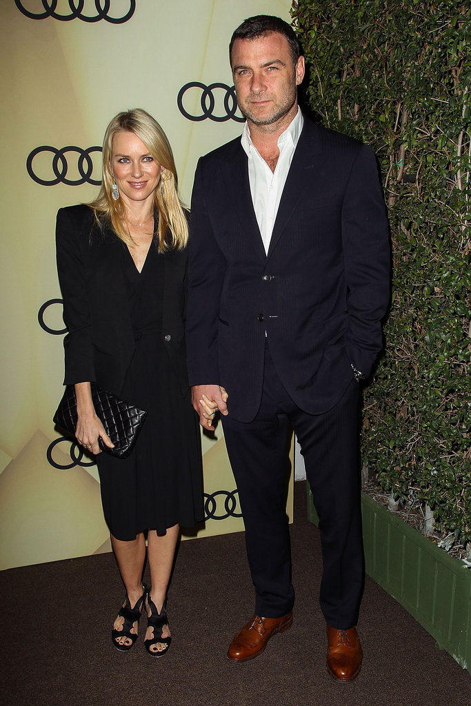 Naomi Watts stuck to a chic black minimalist styling M.O., donning a black cocktail dress with a structured black blazer, a quilted clutch, and cut-out heels.