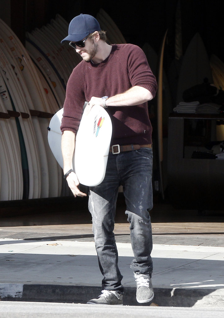 Liam Hemsworth carried a surfboard out of a surf shop in LA.
