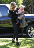 Hilary Duff walked across the lawn with Luca Comrie in her arms.