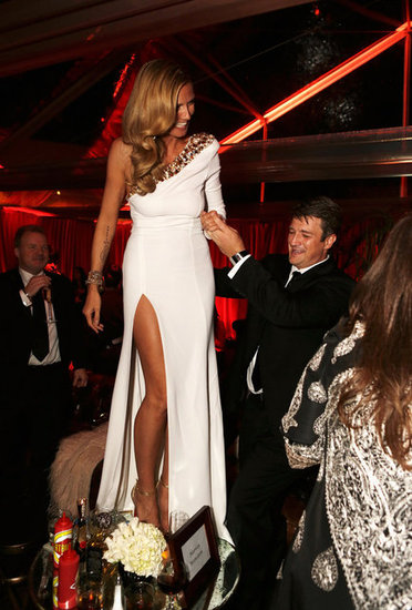 Heidi Klum hopped on a table at the Weinstein Company party with the help of Nathan Fillion.